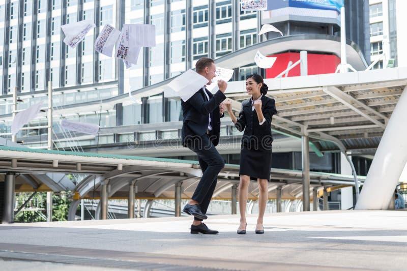 Azjatycki bizneswoman i Kaukaski biznesmena miotanie tapetujemy w powietrzu przesławny dla pomyślnego w misji obrazy royalty free