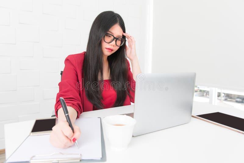 Azjatycki bizneswoman Jest ubranym szkła i czerwony kostium siedzimy a zdjęcia royalty free
