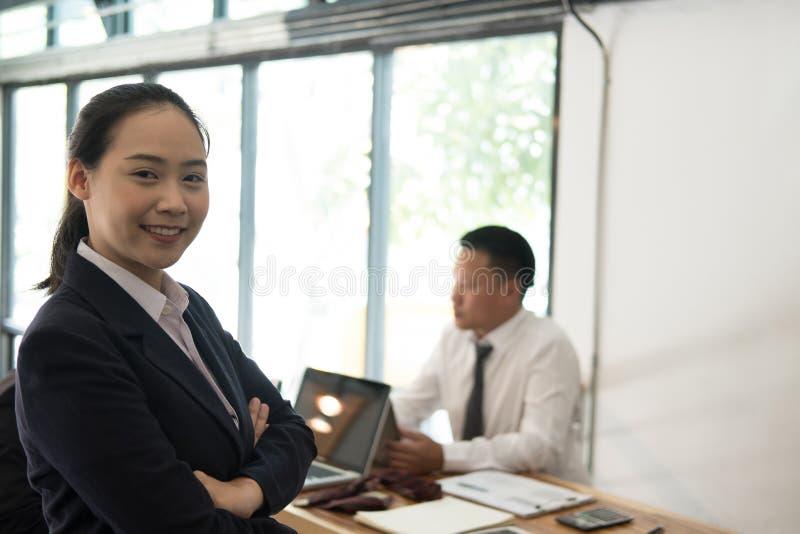 Azjatycki bizneswoman ono uśmiecha się przy kamerą podczas gdy koledzy spotkanie zdjęcie stock