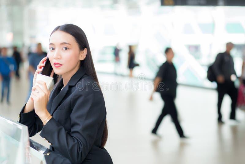 Azjatycki bizneswoman opowiada telefon komórkowego i trzyma filiżankę obrazy royalty free