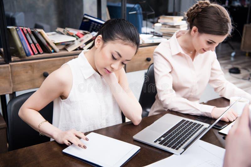Azjatycki bizneswoman pracuje z cyfrową pastylką podczas gdy jej koledzy pracuje blisko w nowożytnym biurze zdjęcia stock