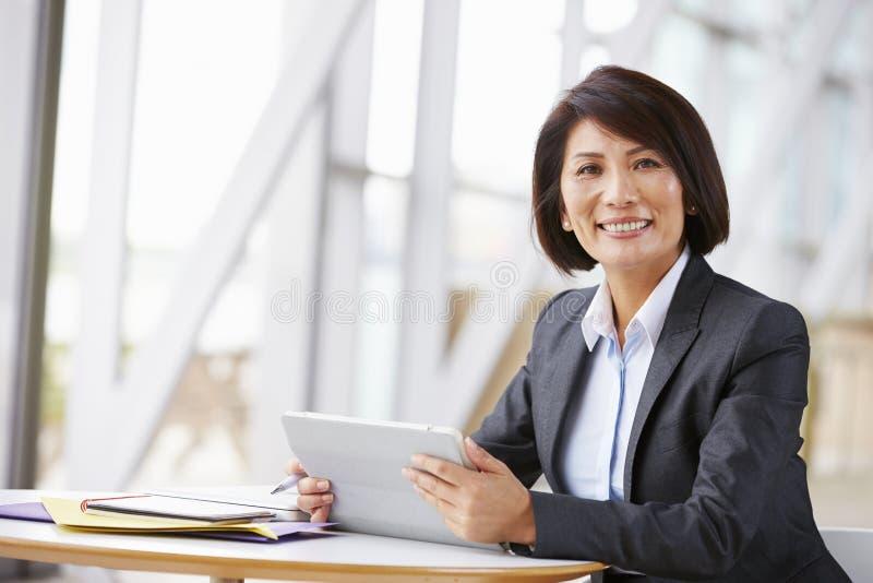 Azjatycki bizneswoman z cyfrową pastylką, ono uśmiecha się kamera obrazy royalty free