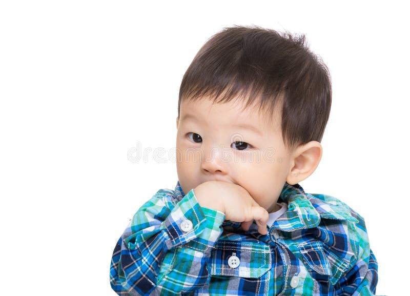 Azjatycki chłopiec kąsek jego ręka zdjęcia royalty free