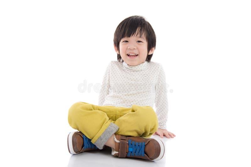 Azjatycki chłopiec obsiadanie na białym tle odizolowywającym obraz royalty free