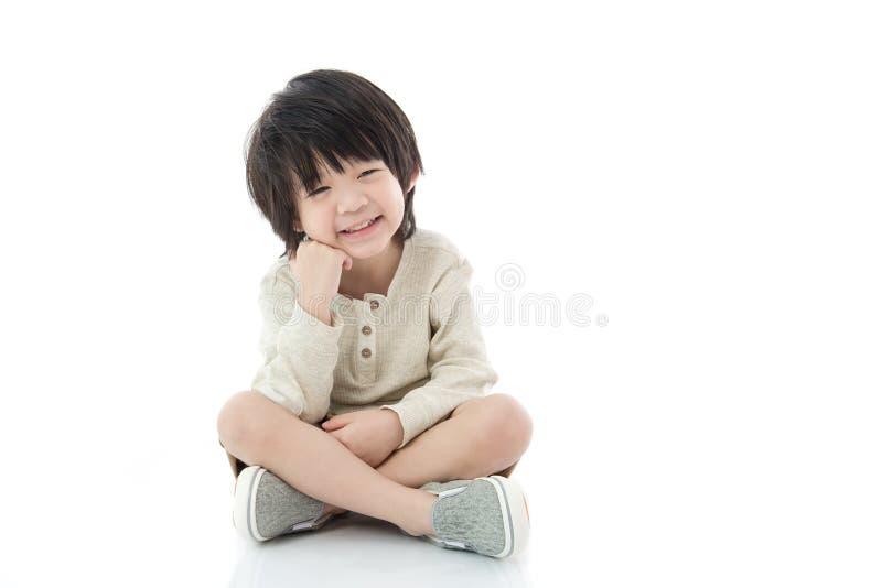 Azjatycki chłopiec obsiadanie na białym tle odizolowywającym fotografia royalty free