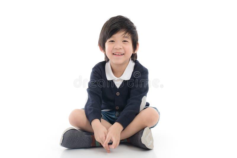 Azjatycki chłopiec obsiadanie na białym tle odizolowywającym obrazy royalty free