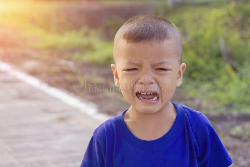 Azjatycki chłopiec płacz na ulicie obrazy stock
