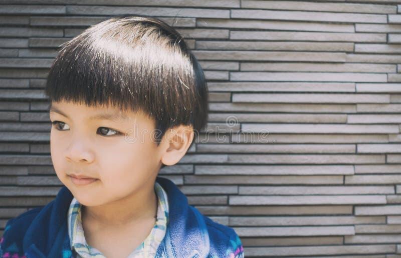 Azjatycki chłopiec potrait na skał płytek ścianie zdjęcie royalty free