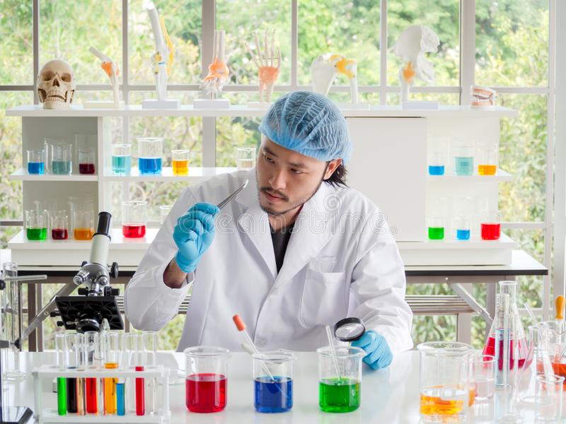 Azjatycki chemika badacz patrzeje pastylkę przy laboratorium naukowiec sprawdza medycynę obrazy stock