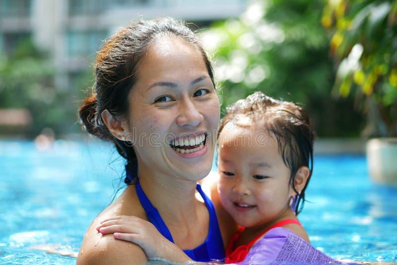 Azjatycki chińczyk córki i matki przytulenie w basenu ono uśmiecha się szczęśliwy zdjęcia royalty free