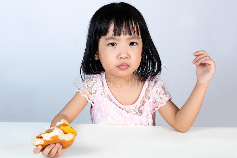 Azjatycki Chiński małej dziewczynki odmawianie Je hamburger obraz royalty free