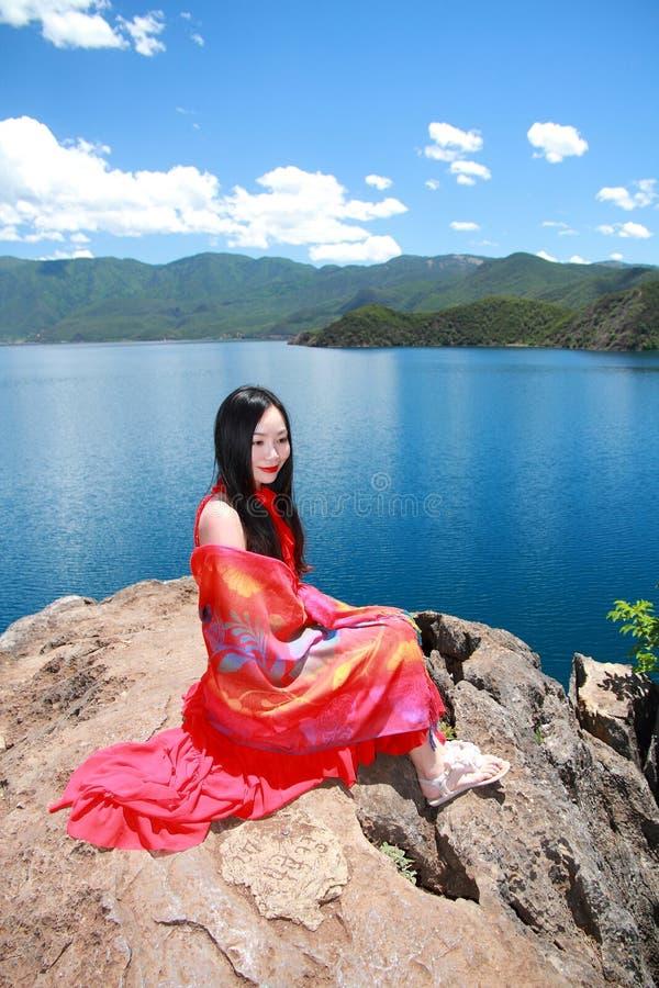 Azjatycki Chiński piękno w czerwieni sukni z czerwonym scraf na głowie, Siedzi w kamieniu przy Yunnan Lugu jeziora plażą, cieszy  zdjęcia royalty free