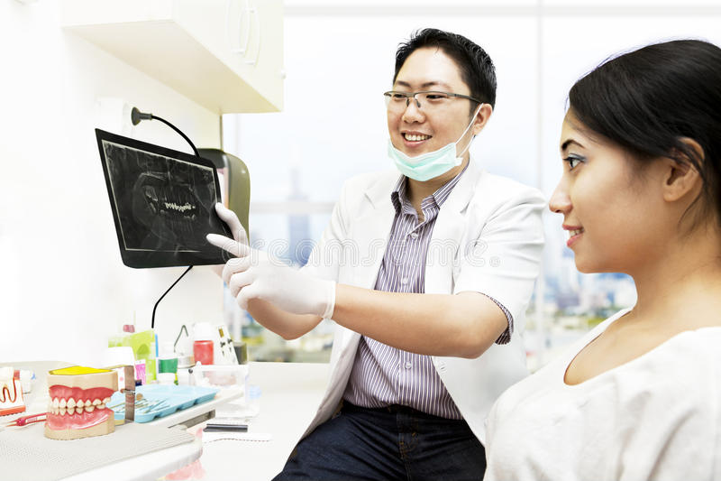 Azjatycki dentysta z promieniowaniem rentgenowskim i pacjentem zdjęcia royalty free