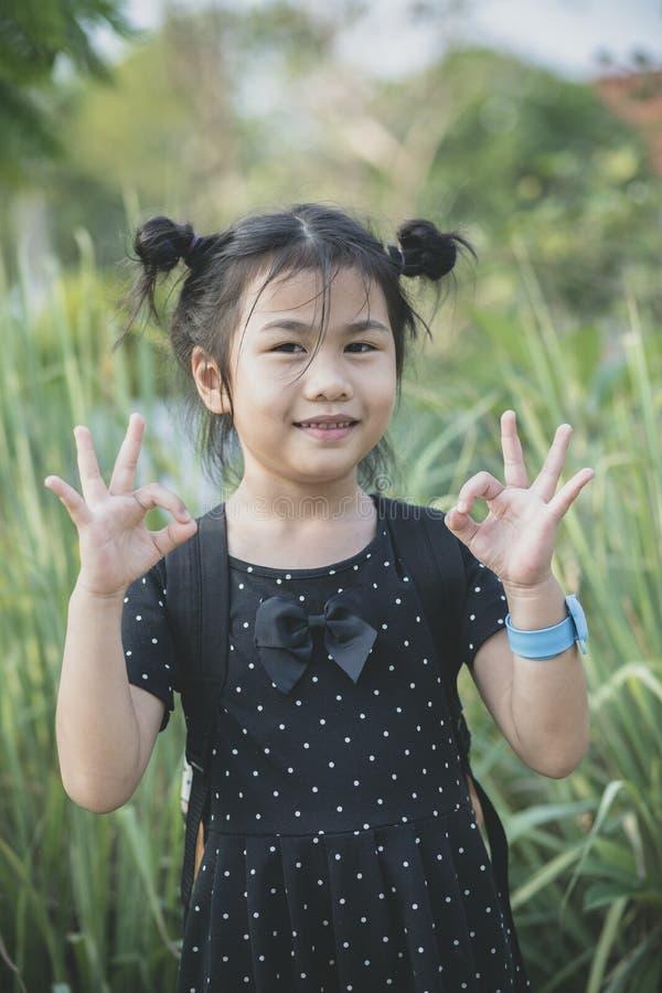 Azjatycki dzieci stać plenerowy i wręcza znaka wszystko prawy, ok obraz royalty free