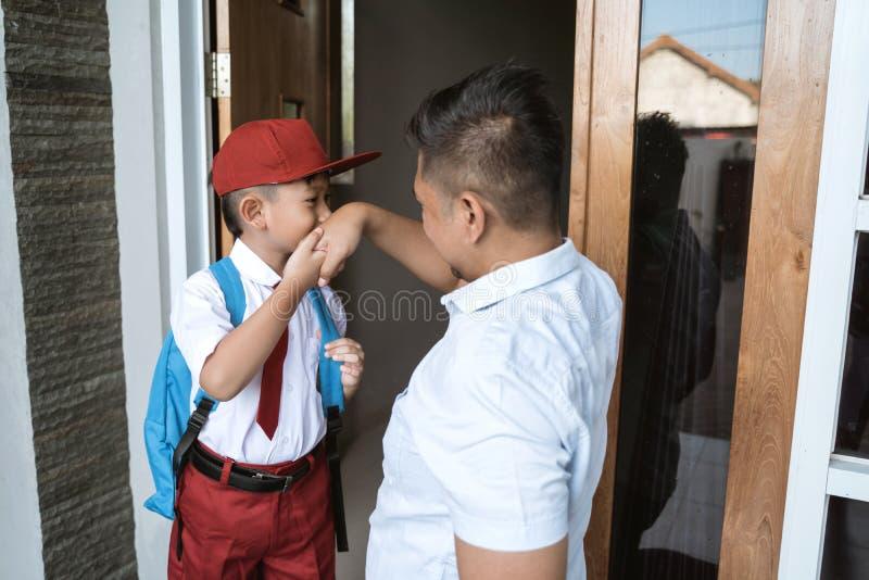 Azjatycki dzieciak całuje jej ojca rękę przed iść szkoła zdjęcie stock