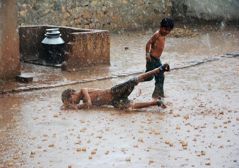 Azjatycki dzieciak spadał na śliskim zmielonym bieg w ulewnym deszczu zdjęcie stock