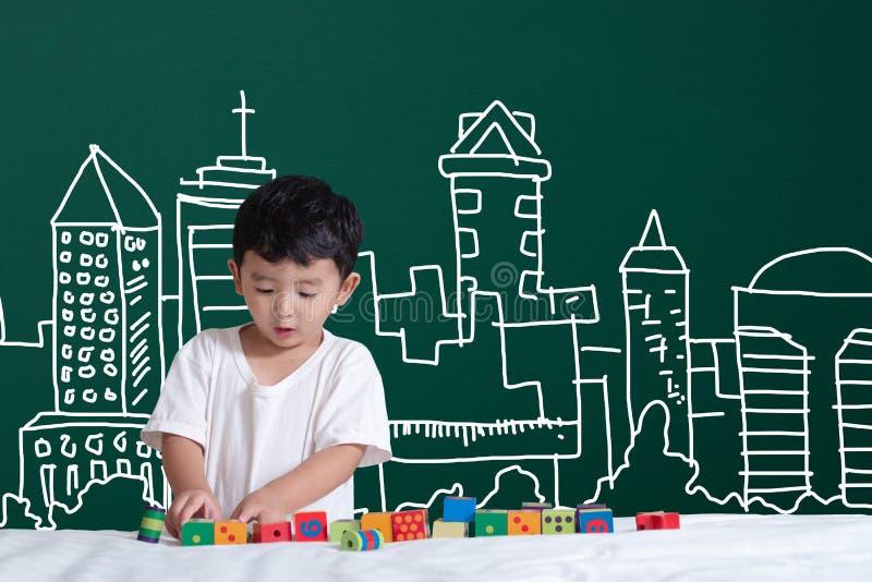 Azjatycki dzieciaka uczenie bawić się z jego wyobraźnią o buildin zdjęcia royalty free