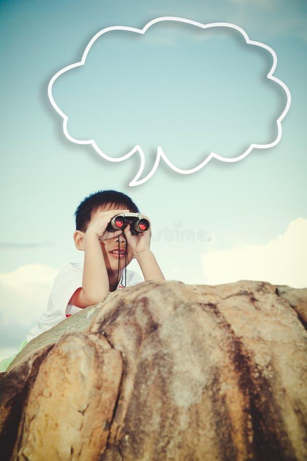 Azjatycki dziecko cieszy się lornetki z pustą chmurą na niebieskim niebie vi zdjęcia stock