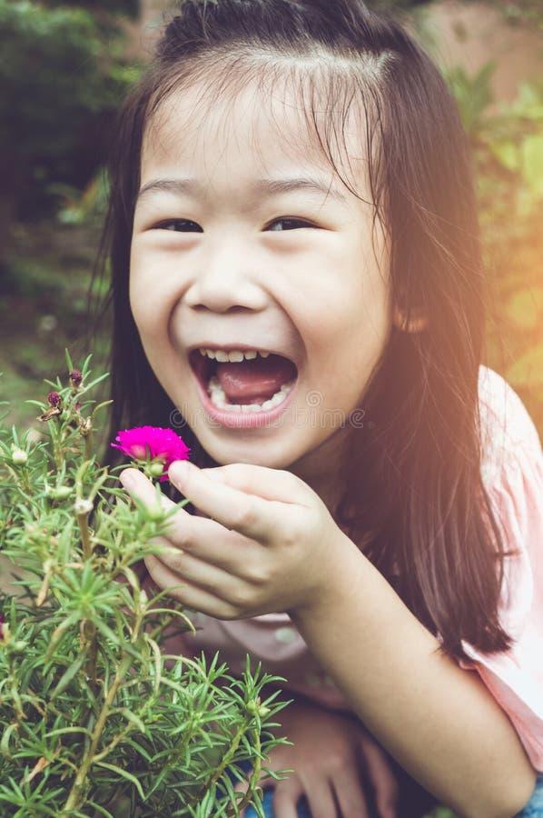 Azjatycki dziecko podziwia dla menchii natury i kwiatów wokoło przy backy zdjęcie royalty free