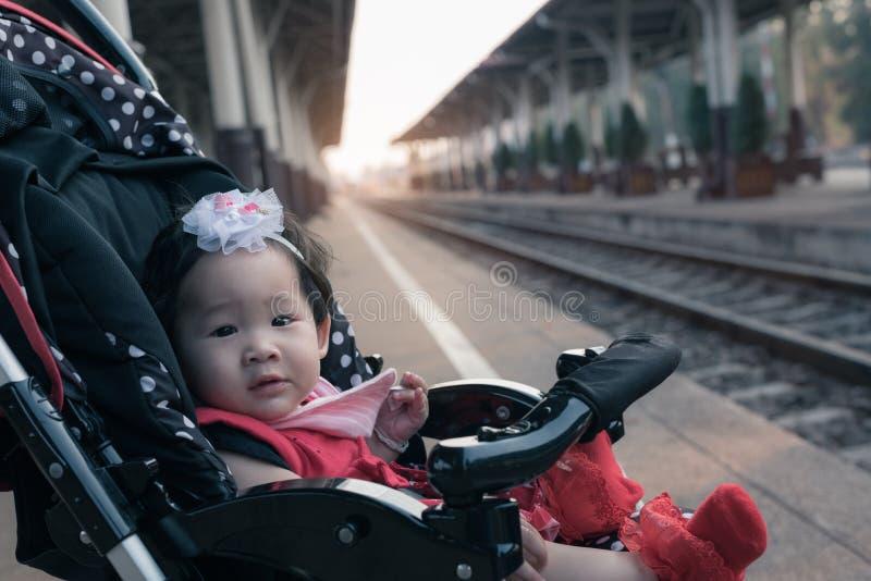 Azjatycki dziewczynki obsiadanie w spacerowiczu w staci kolejowej obrazy stock