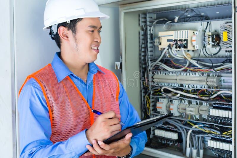 Azjatycki elektryk przy panelem na budowie zdjęcia royalty free
