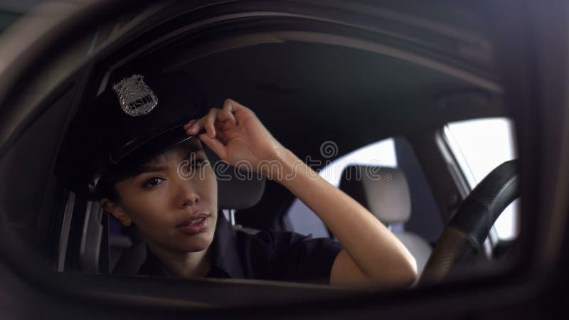 Azjatycki funkcjonariusz policji przystosowywa jej jednolitą nakrętkę patrzeje w rearview lustro zdjęcia royalty free