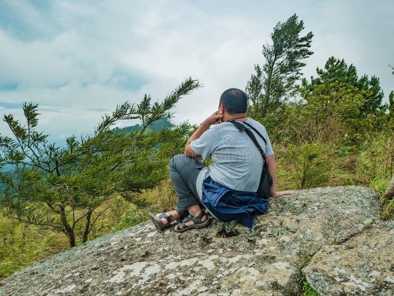Azjatycki Gruby Trekker siedzi na kamieniu przy Khao Luang górą w Ramkhamhaeng parku narodowym obrazy royalty free
