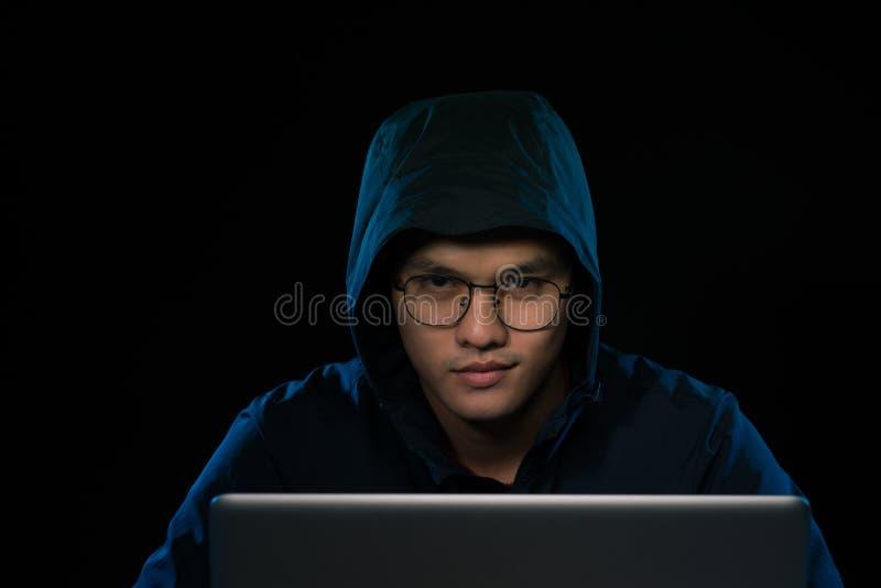 Azjatycki hacker sieka sieć komputerową z laptopem w zmroku Cyber zdjęcia royalty free