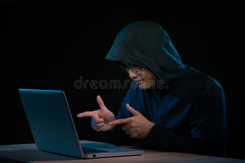 Azjatycki hacker sieka sieć komputerową z laptopem w zmroku Cyber obraz stock