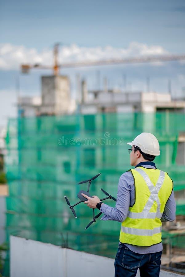 Azjatycki inżyniera mężczyzna używa trutnia dla miejsce ankiety obraz stock