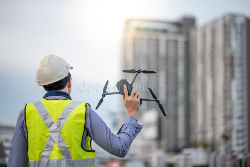 Azjatycki inżyniera mężczyzna używa trutnia dla miejsce ankiety zdjęcia stock