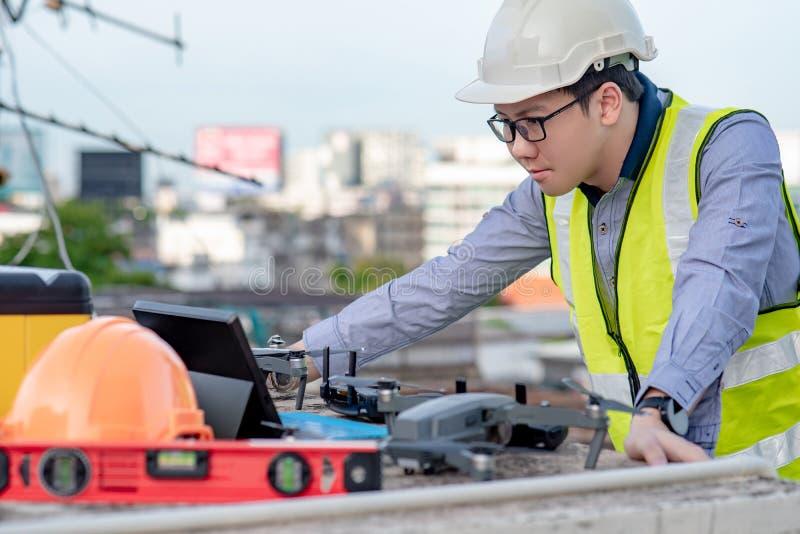 Azjatycki inżyniera mężczyzna używa trutnia dla miejsce ankiety zdjęcie royalty free