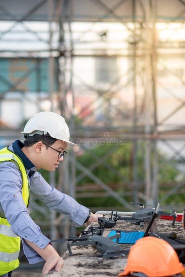 Azjatycki inżyniera mężczyzna używa trutnia dla miejsce ankiety zdjęcia royalty free