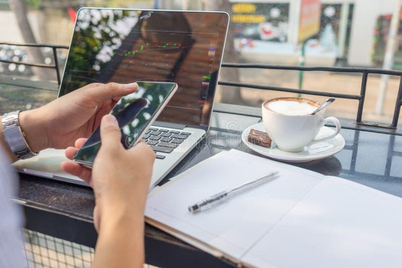 Azjatycki inwestor ogląda zmianę rynek papierów wartościowych na laptopie i smartphone zdjęcia stock