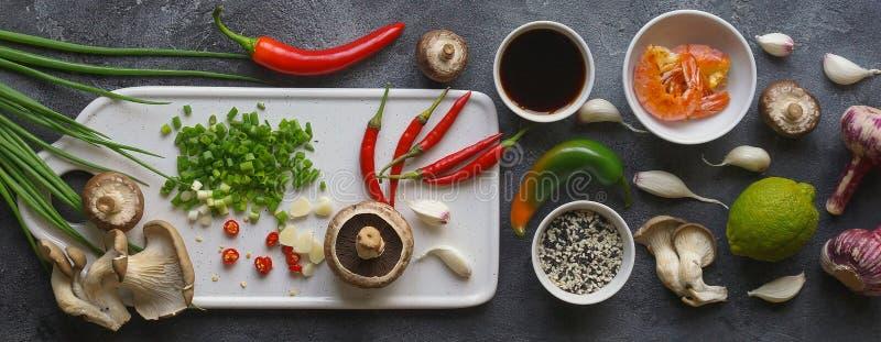Azjatycki jedzenie na ciemnym tle, Wok ryż z garnelami i pieczarki, Podczas przygotowania, sztandar, składniki zdjęcia royalty free