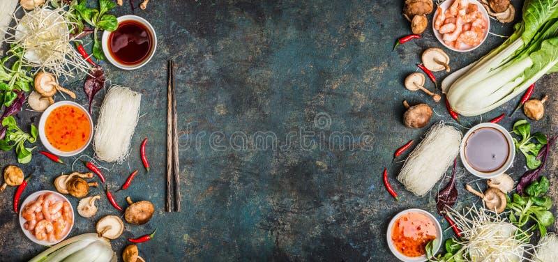 Azjatycki karmowy tło z różnorodnym kulinarni składniki na nieociosanym tle, odgórny widok obrazy stock