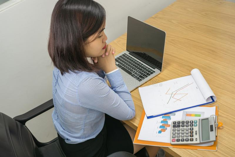 Azjatycki kierownik czyta pieniężnego raport i działanie na laptopie obrazy royalty free
