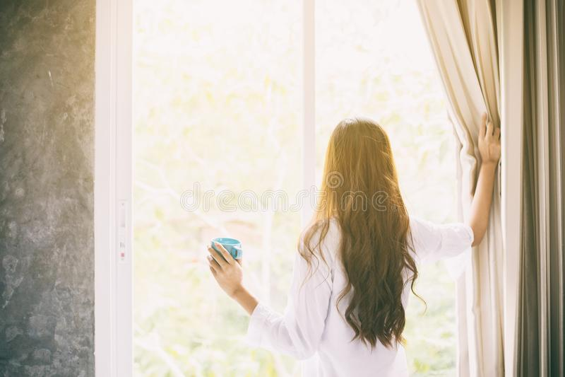 Azjatycki kobiet pić kawowy w jej łóżka reste up i budzić się w pełni zdjęcie royalty free