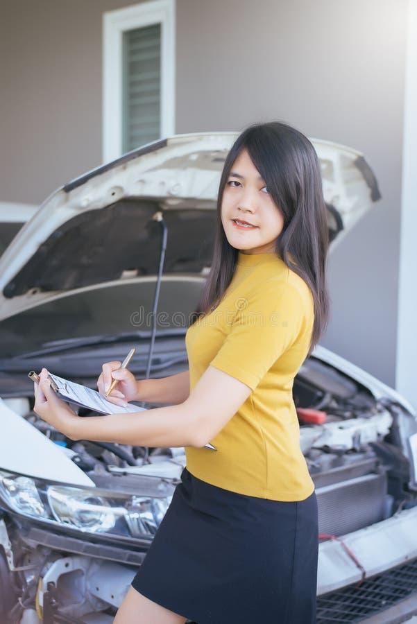 Azjatycki kobieta personel sprawdza samochód z schowkiem zdjęcie royalty free