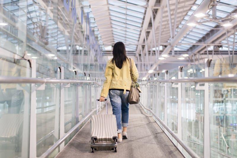 Azjatycki kobieta podróżnika dolezienie niesie na bagaż walizce przy lotniskowym korytarzem chodzi wyjściowe bramy fotografia royalty free