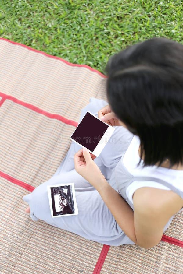 Azjatycki kobieta w ciąży przedstawienia ultradźwięku filmu dziecka obrazek na ona był zdjęcia royalty free