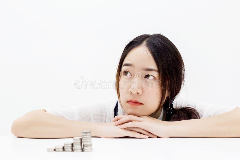 Azjatycki kobiety główkowanie podczas gdy tam są monety brogujący up w przodzie w białym odosobnionym tle - inwestycja, finanse, zdjęcia stock