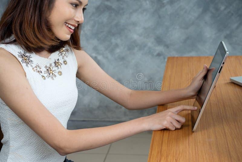 Azjatycki kobiety obsiadania uśmiech używa jej pastylkę obrazy stock