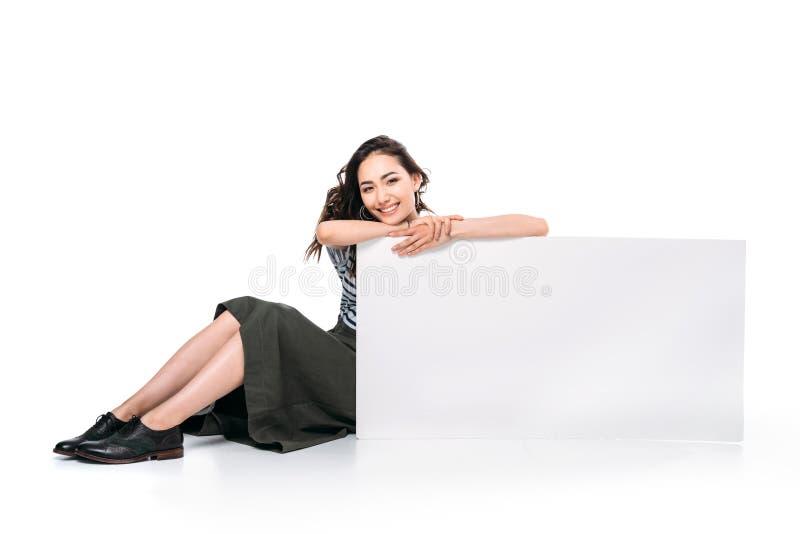 Azjatycki kobiety obsiadanie i patrzeć kamerę podczas gdy trzymający puste miejsce deskę obrazy stock