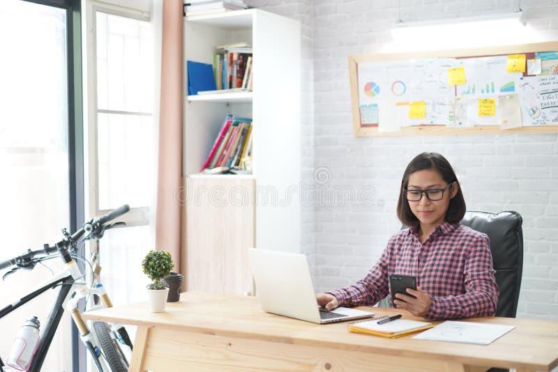 Azjatycki kobiety obsiadanie w eleganckim mienia smartphone z pracować na laptopie zdjęcie royalty free