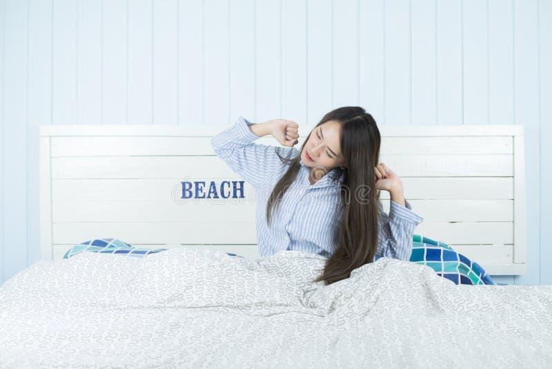 Azjatycki kobiety rozciąganie w łóżku po budził się w ranku przy sypialnią po budzić się up w jej łóżku w pełni odpoczywającym obrazy royalty free