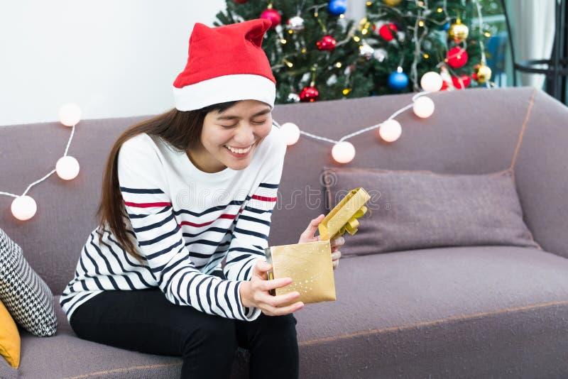 Azjatycki kobiety zakończenia oko gdy otwarty złota xmas prezenta pudełko przy wakacje pa obraz stock