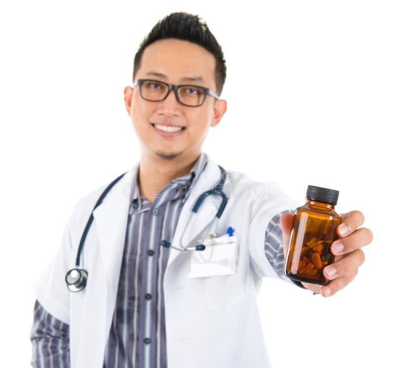 Azjatycki lekarz medycyny trzyma butelkę pigułki zdjęcia stock