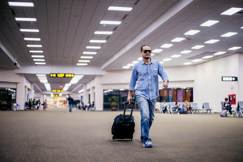 Azjatycki mężczyzny podróżnik z walizek chodzić przy lotniskiem i transport zdjęcia stock