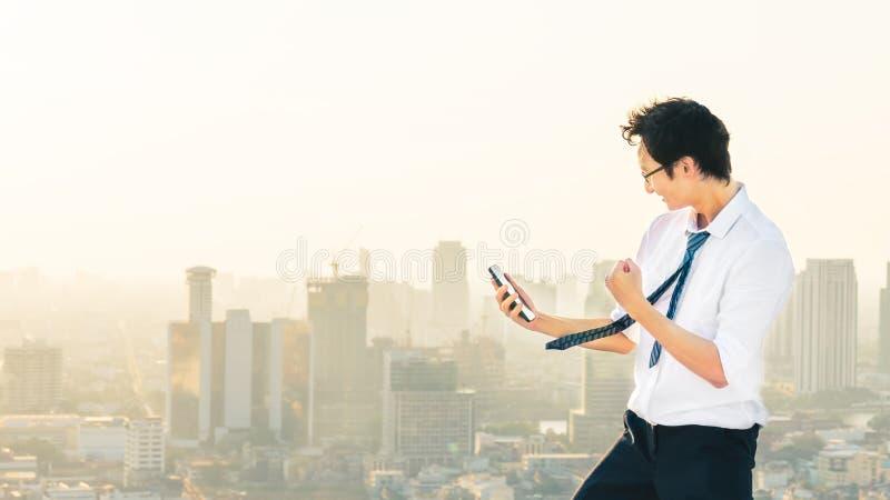 Azjatycki mężczyzna świętuje z smartphone, sukcesu lub dopingu pozą na dachu zmierzchu miasta scenie, zdjęcia royalty free